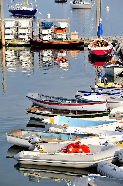 Busy Rockland Harbor with colorful sailboats, rowboats, skiffs, and motorboats, and colorful reflections in water. Rockland, Maine, USA.