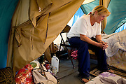 RENO, NV - OCTOBER 6:  Mary Jackson sits in her tent in a tent city for the homeless in downtown Reno, Nevada October 6, 2008. Jackson works odd jobs and her husband, a veteran, works 18 hours per week, but they're unable to make enough money to afford housing. The City of Reno set up the tent city when existing shelters became overcrowded as Nevada struggles with one of the highest unemployment rates in the country. (Photo by Max Whittaker/Getty Images)