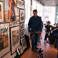 """People and their dogs gather in the Robert McClintock Studio & Gallery to mingle and look at artwork by the local artist, 1809 Thames Street, Baltimore, Maryland, USA.  The artist melds photography and digital painting to create his vibrant """"Baltimore Seen"""" works and other collections of work including portraits of dogs."""