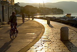 Europe, Croatia, Dalmatia, Hvar Island, Stari Grad town.  Promenade by harbor at sunset.