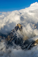 A view on Aiguille du Midi with dense clouds passing next to this iconic summit on a stormy Summer afternoon, taken from Aiguille Gouter, Chamonix, France.