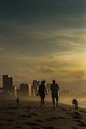 A couple and their dogs walking at Leblon beach during the early hours of the morning. Rio de Janeiro, Brazil.