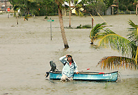 A man pulls his boat through the completely flooded town of Everglades City, Florida after Hurricane Wilma hit October 24, 2005. Everglades City took a direct hit from the storm as it came ashore.