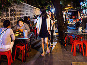 24 MARCH 2017 - BANGKOK, THAILAND: Pedestrians walk between tables of a restaurant that is set up on the sidewalk of Sukhumvit Soi 55 (Thong Lo). The restaurant is being evicted from its location. Food cart vendors along Sukhumvit Road between Sois 55 (Thong Lo) and 69 (Phra Khanong) in Bangkok have been told by city officials that they have to leave the area by 17 April. It's a part of an effort by Bangkok city government, supported by the ruling junta, to take back the city's sidewalks. The evictions in the area are the latest in mass evictions of Bangkok street food vendors after similar actions elsewhere on Sukhumvit, in the Ari area, in Silom/Patpong and Ratchaprasong neighborhoods. The vendors in Thong Lo/Phra Khanong are popular with local office workers because most of the formal restaurants in the area serve foreign tourists and upper class Thais and are very expensive. The street food carts serve meals starting at about 35Baht ($1US). The city has not announced if they will provide alternative locations for the carts.     PHOTO BY JACK KURTZ