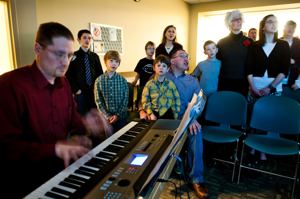 John Hanson playing the piano at Oikos Community Church while his children and other members of the congregation sing during the Sunday service...John is currently unemployed after recently coming back from military duty in Iraq - he is part of the National Guard.