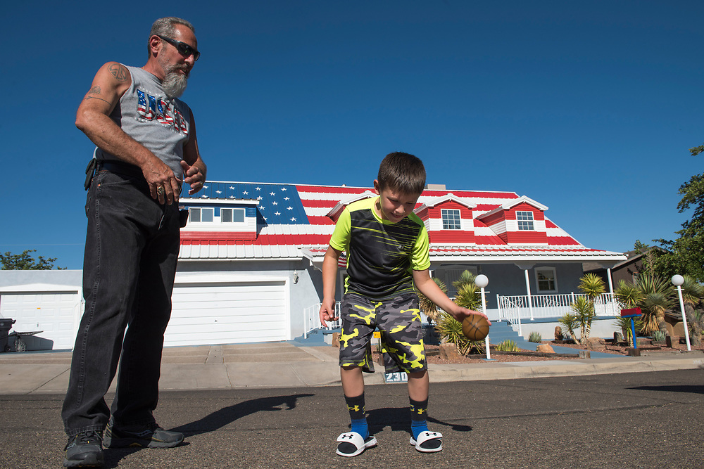 rer062817c/A1/June 28, 2017/Albuquerque Journal<br />  Rick Gabaldon(Cq) has displayed an American flag on the roof of his house on his West Mesa house in Albuquerque.  The image stretched the entire length of the roof. Pictured is Rick with his grandson Richard Gabaldon III(cq) dribbling a mini basketball on a late afternoon. <br /> Albuquerque, New Mexico Roberto E. Rosales/Albuquerque Journal