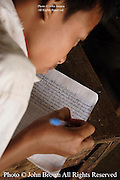 A student at The Ban Buamlao Primary School in Ban Buamlao, Laos, transcribes notes from a textbook to a workbook.  Since many of the students are without textbooks, they construct their own using this method.