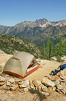 Backpacking tent on ridge above Cutthroat Pass, near Pacific Crest trail. Silver Star Mountain is in the distance. North Cascades Washington