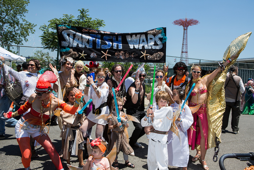 """Brooklyn, NY - 18 June 2016. A  group of people with Star Wars-themed costumes poses under a banner that reads """"Starfish Wars."""""""