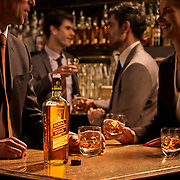 Royal Stag whisky bottle and glasses on a bar top with models in the background Ray Massey is an established, award winning, UK professional  photographer, shooting creative advertising and editorial images from his stunning studio in a converted church in Camden Town, London NW1. Ray Massey specialises in drinks and liquids, still life and hands, product, gymnastics, special effects (sfx) and location photography. He is particularly known for dynamic high speed action shots of pours, bubbles, splashes and explosions in beers, champagnes, sodas, cocktails and beverages of all descriptions, as well as perfumes, paint, ink, water – even ice! Ray Massey works throughout the world with advertising agencies, designers, design groups, PR companies and directly with clients. He regularly manages the entire creative process, including post-production composition, manipulation and retouching, working with his team of retouchers to produce final images ready for publication.