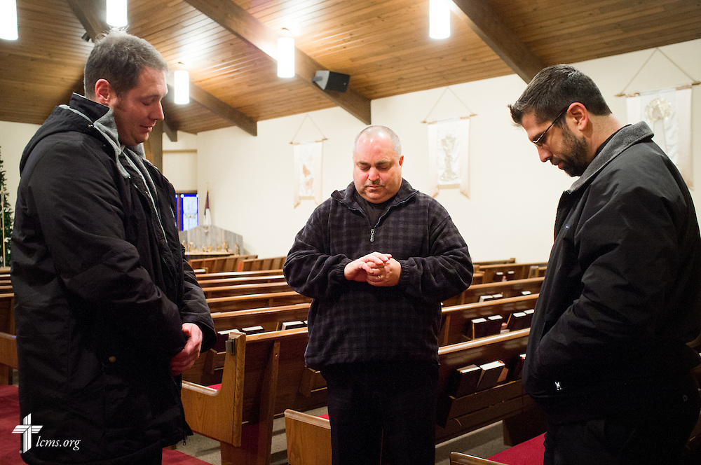 Rev. Thomas Heren (center) of Our Savior Lutheran Church in Washington, Ill., prays with Rev. Michael W. Meyer, manager of LCMS Disaster Response (left), and  Rev. Ross E. Johnson (right), director of LCMS Disaster Response, on Wednesday, Dec. 18, 2013.  Nearly two dozen tornadoes plowed through Illinois in November, killing a total of seven. The damaged LCMS church served as a relief center for members and nearby residents. LCMS Communications/Erik M. Lunsford