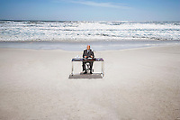 Businessman Sitting at an Office Desk at the Beach