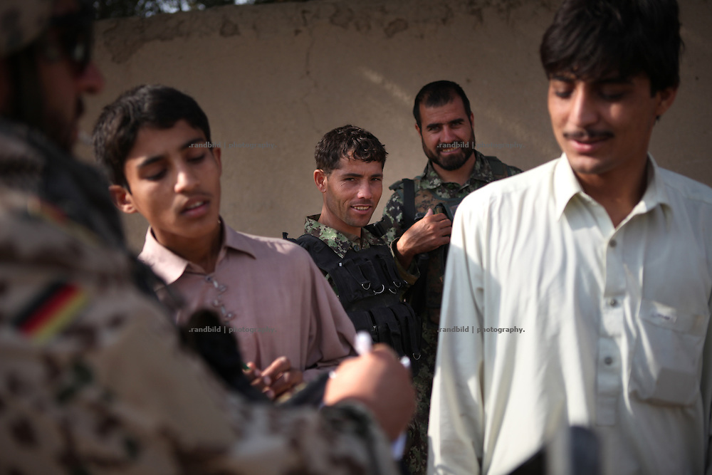 ANA-soldiers watches germans talking to afghans. Joint patrol of german Bundeswehr and Afghan National Army in and around Nawabad. By rising presence ISAF wants to push out remain Taliban and occupy the former insurgent held region of Chahar Darah. Soldiers talk to local, recruit informers, check cars and try to figure out essential needs of Nawabads local polupaltion. late October 2011 Kunduz based 3.Task Force started a several days operation in and around Nawabad (District Chahar Darah), west of Kunduz, northern Afghanistan. During the Operation Orpheus about 100 german infantery soldiers rolled out for patrols through the town and surrounding areas, which were expected as a retreat zone of insurgents.