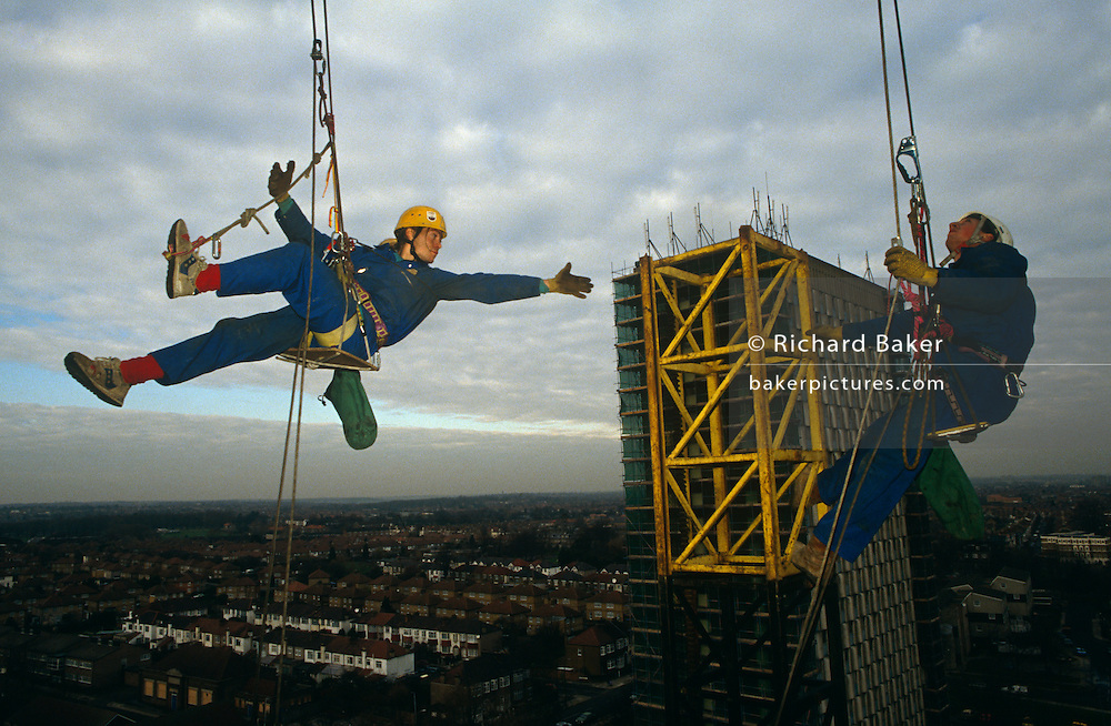 Reaching out to a tower of scaffolding, high above the skyline of North London, a member of a company of abseiling construction scaffold workers make use of circus skills. Suspended with ropes, carabinas and a seat harness normally used by mountaineers, this man is wearing a safety helmet and blue overalls and his dirty gloved hand is about to make contact with yellow iron work as his colleague looks skyward, already tethered to the reinforced structure. A 60s tower block is immediately behind and suburban houses and streets are below. We see a man about to make contact with a place of safety, reaching out to his destination while spread across London's skies. Lit by flash, this picture is confusing because the viewer sees a false sense of size and scale between the iron work and the flats behind.