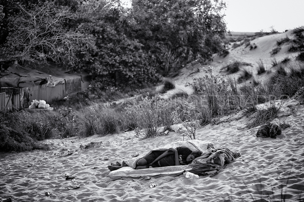 A homeless woman who used to squat in a condemned house in Kennedy Hill, is now sleeping in the sand dunes as the dwelling was demolished the previous day.  A lack of affordable short-term accommodation, combined with Aboriginal people moving in from remote communities, has led to people camping on bush blocks and parks in town. Broome, Western Australia. ©Ingetje Tadros/Diimex