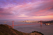 The Golden Gate Bridge and San Francisco, California shot from the Marin Headlands one night at sunset, capturing vibrantly pink sunset colors.
