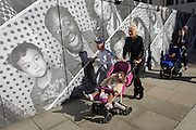 A woman pushes a child in a buggy past a construction hoarding featuring many faces and expressions.