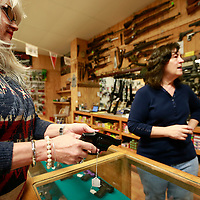 Thomas Wells | BUY AT PHOTOS.DJOURNAL.COM<br /> Kathy Baliey, left, looks over several different handgun types at Carr's Gun Shop in Saltillo on Thursday.