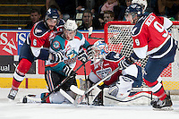 KELOWNA, CANADA - MARCH 23: Ryan Olsen #27 of the Kelowna Rockets is checked by Justin Hamonic #6 as Eric Comrie #1 of the Tri-City Americans makes a save on March 23, 2014 at Prospera Place in Kelowna, British Columbia, Canada.   (Photo by Marissa Baecker/Shoot the Breeze)  *** Local Caption *** Ryan Olsen; Justin Hamonic; Eric Comrie;