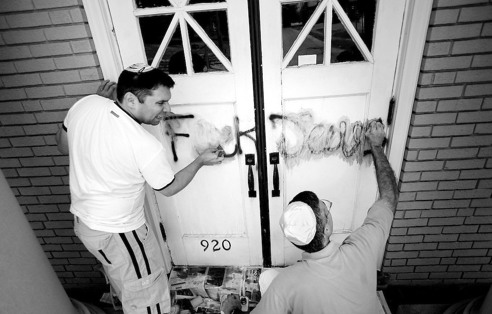 Kyle Green | The Roanoke Times<br /> July 27, 2009 - Rabbi Fabian Werbin (left), and Synagogue member, Gary Karesh, use paint remover to scrub the words &quot;Fuck Jews&quot; off of the front door of the Beth Israel Synagogue on Franklin Road in Roanoke , Virginia.