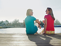 Two women sitting on pier back view