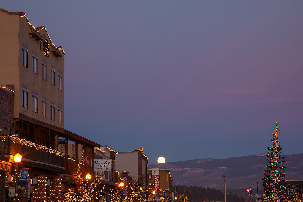 """""""Moon Over Truckee 1"""" - Photograph of a moon rising over Truckee at sunset. An alpenglow sunset and Christmas lights compliment the moon."""
