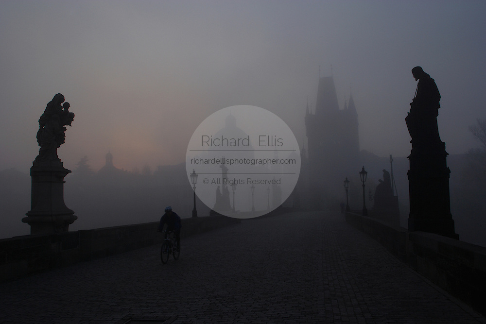 Pedestrians walk across the historic Charles Bridge built in the 14th century with rows of Baroque statues blanketed in fog in  Prague, Czech Republic.