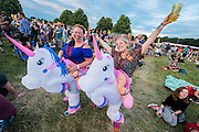 Inflatable unicorn costunmes for a birthday girl and her friend - The 2016 Latitude Festival, Henham Park, Suffolk.