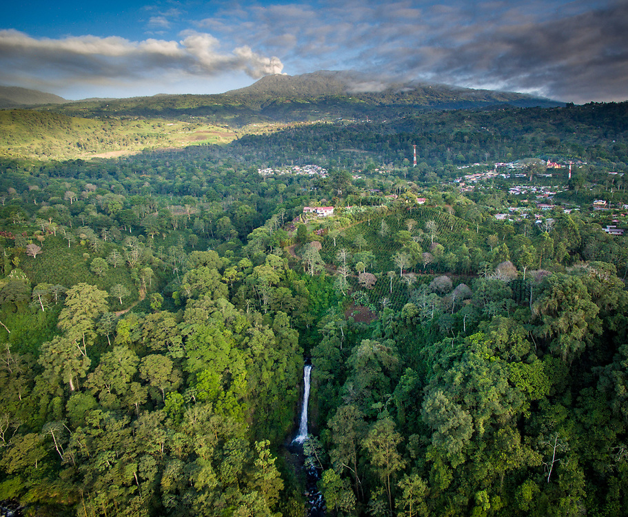 An aerial view of the town of Aquires, the Aquires waterfall, and the Turrialba volcano located in the Costa Rican jungle.