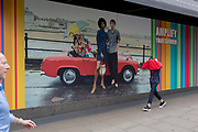 A young man walks past a House of Fraser billboard ad while pulling on his red top back on, on 30th May 2019, in London, England.