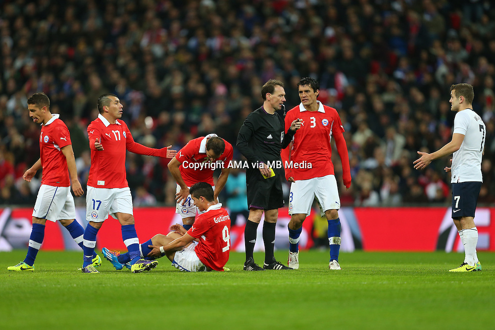 Gary Medel of Chile and Jack Wilshere of England shrug their shoulders at each other as the Chile team talk to Referee Florian Meyer of Germany