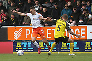 Luton Town forward James Collins (19) is held by Burton Albion defender Kyle McFadzean (5) during the EFL Sky Bet League 1 match between Burton Albion and Luton Town at the Pirelli Stadium, Burton upon Trent, England on 27 April 2019.
