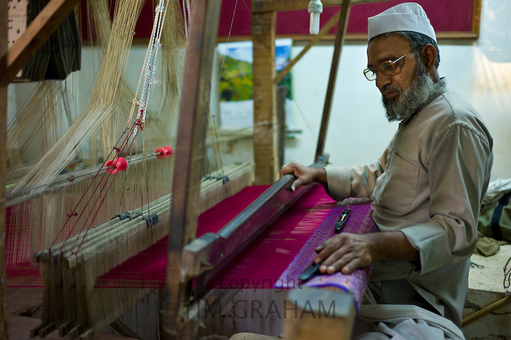 Indian man working loom at silk factory making textiles and saris at Bressler near Varanasi, Benares, Northern India RESERVED USE - NOT FOR DOWNLOAD -  FOR USE CONTACT TIM GRAHAM