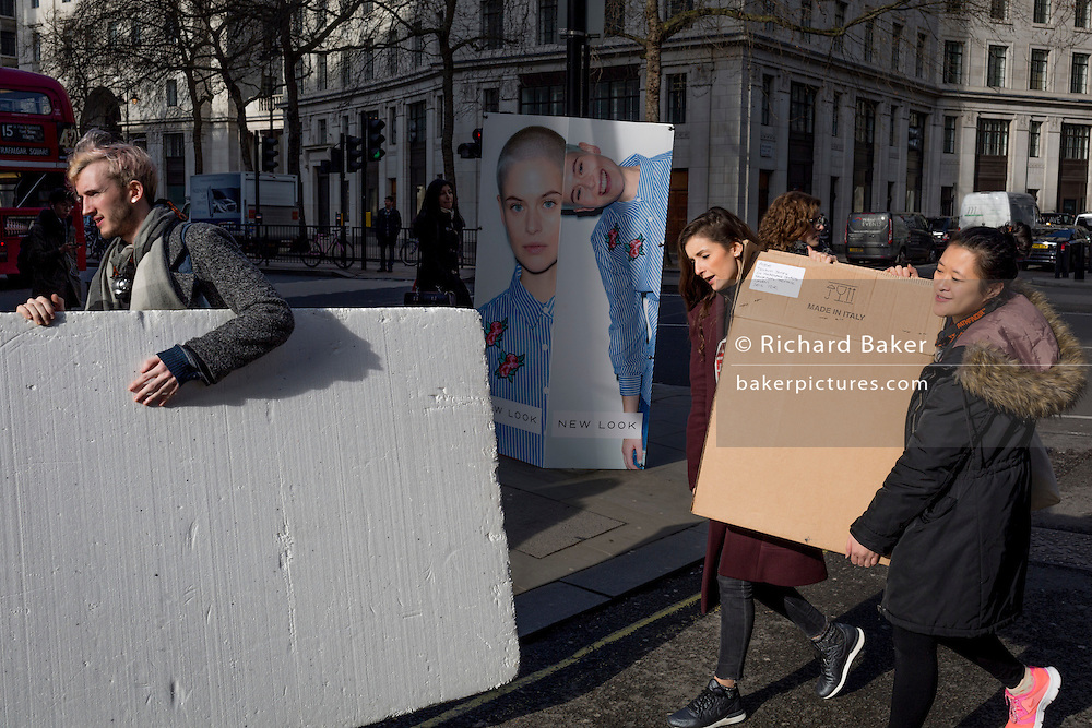 """The crew of a fashion house carry boards and equipment outisde London Fashion Week in the Strand, on 17th Febriary 2017, in London, England, United Kingdom. London Fashion Week is a clothing trade show held in London twice each year, in February and September. It is one of the """"Big Four"""" fashion weeks, along with the New York, Milan and Paris. The fashion sector plays a significant role in the UK economy with London Fashion Week alone estimated to rake in £269 million each season. The six-day industry event allows designers to show their collections to buyers, journalists and celebrities and also maintains the city's status as a top fashion capital. (Photo by Richard Baker / In Pictures via Getty Images)"""