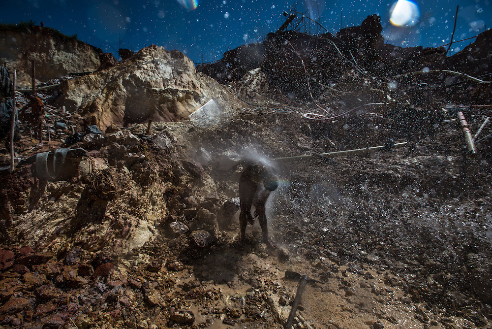 "LAS CLARITAS, VENEZUELA - JULY 20, 2016:  A miner gets sprayed by a powerful water hose to clean off the mud covering his body.  Thousands of Venezuelans are flocking to illegal gold mines, like this one, called ""Cuatro Muertos"" (""Four Dead"" because four miners have died here since the mine was dug) in hopes of surviving the current economic crisis by earning in gold instead of the national currency, whose value steadily falls due to the world's highest inflation.  From this remote part of the jungle the migrant miners have become the vectors of a new epidemic of malaria, because the hot, swampy conditions of the mines make for an ideal breeding ground for mosquitos. Miners spread the disease as they return home with earnings or pay visits to family members. Dozens of miners that work in this mine said that they have contracted malaria multiple times, some even dozens of times. The economic crisis has also left the government without the financial resources to control the disease - they are unable to fumigate homes, provide medicines to everyone that is sick, or even to test all patients with symptoms of malaria in many places. PHOTO: Meridith Kohut"