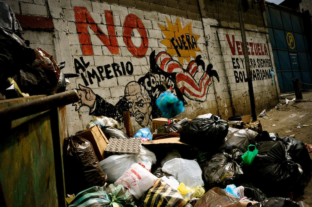 Trash overflows a dumpster in the El Junquito slum in Caracas, Venezuela. People living in Venezuelan slums are faced daily with inadequate municipal services, including water and electricity shortages, poor roads and an unreliable waste management system.
