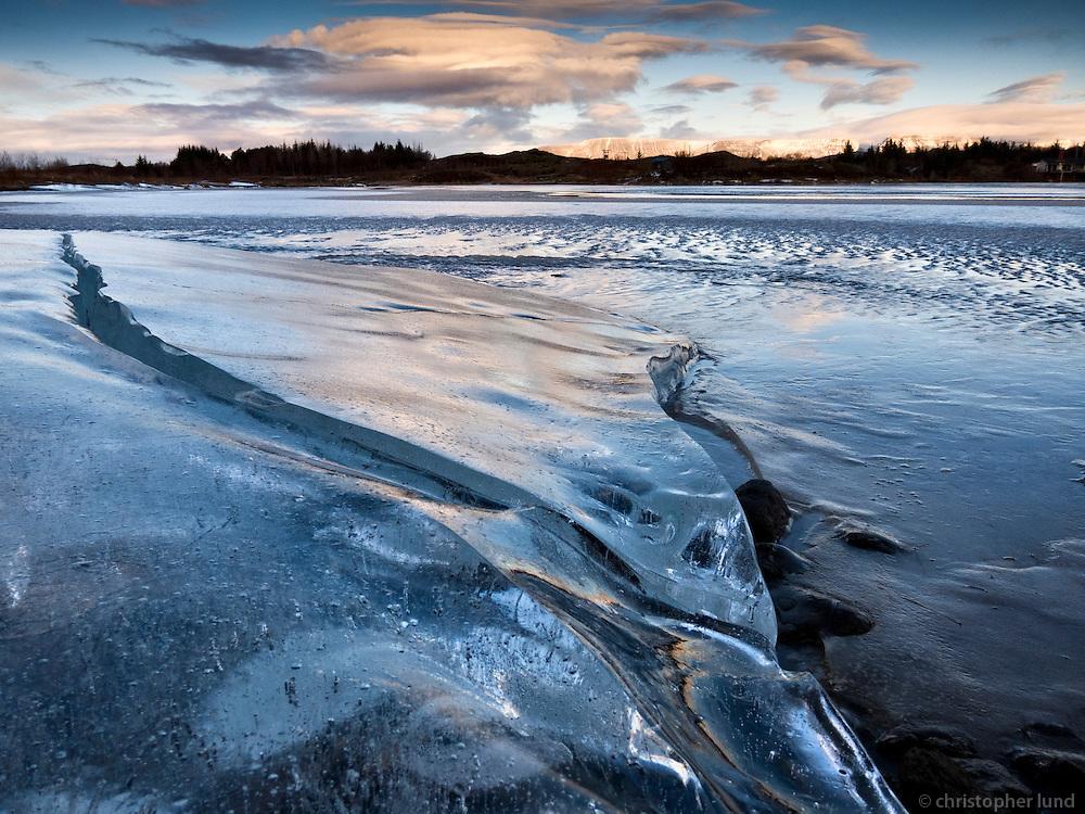 Lake Elliðavatn in winter, partly frozen. Blue ice in foreground and warm light on mountains and clouds in background. Elliðavatn að vetri til. Blár ís í forgrunni og heit birta á fjöllum og skýjum í baksýn.