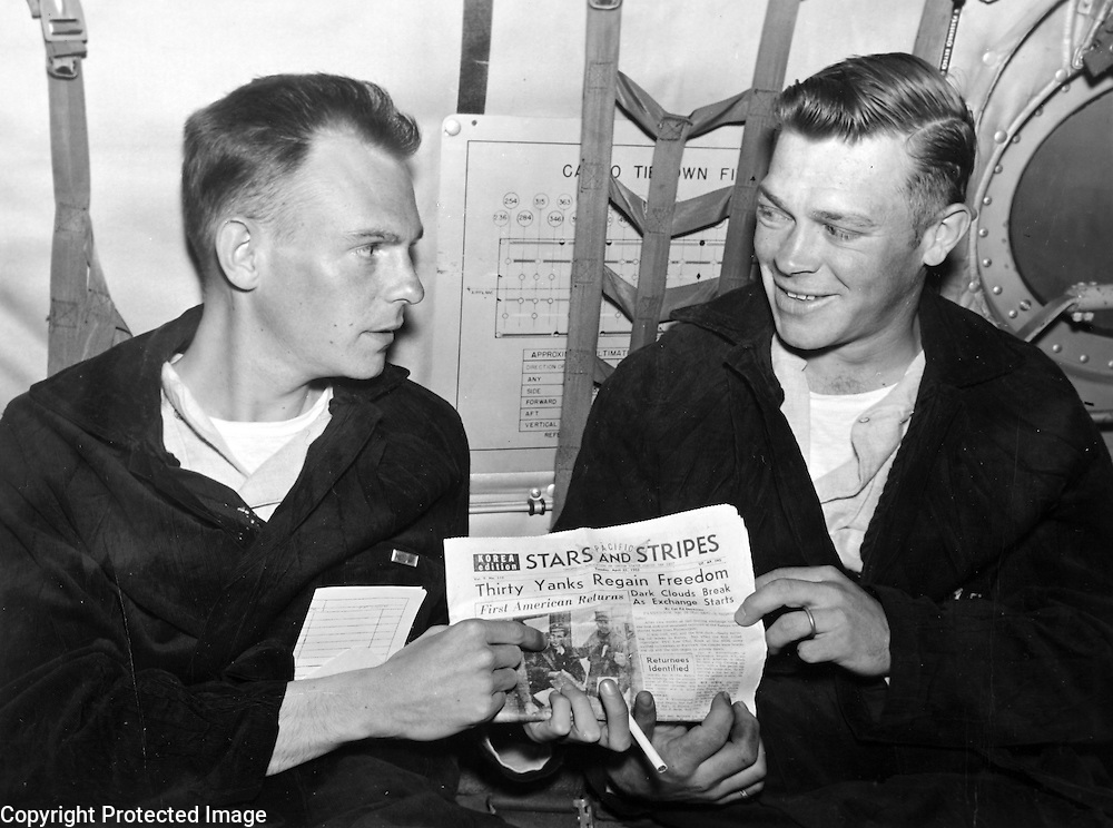 """Combat Cargo, en route to Japan --- 1st Lt. Roy M. Jones (left) and Sgt. Gerald Neighbors looks over a Seoul edition of Stars and Stripes, listing their names as UN returned sick and wounded personnel. They were on the first Combat Cargo U.S. Air Force C-124 """"Globemaster"""" flight bringing the repatriates on the first leg of their flight home -- from Seoul to Tokyo. Lt. Jones, a 1st Cavalry Division platoon leader, was captured on November 1, 1950. Sgt. Neighbors, a quad leader in the 38th Infantry Regiment of the 2nd Division, was captured 29 months ago. April 1953."""