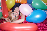 Portrait of teenage girl (16-17) lying on bed under pile of balloons