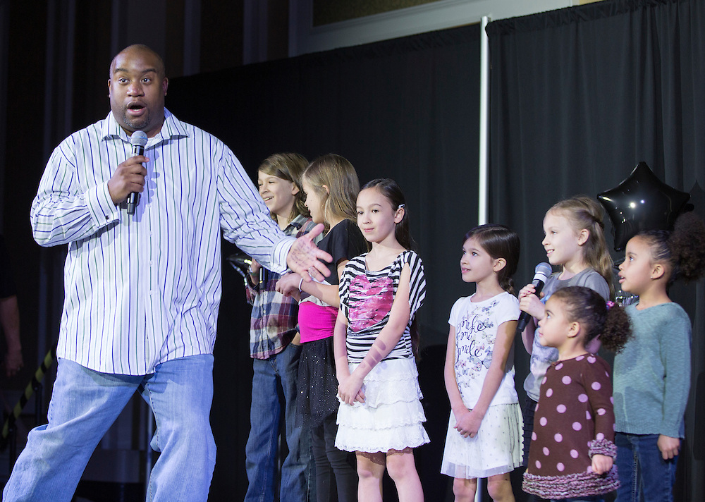 """Jamie Patton, Assistant Dean of Students, performs """"We are the World"""" with his family during the Faculty Pageant on February 22, 2016. Patton placed first at the pageant."""