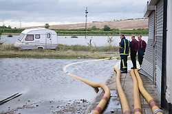 Members of the fire rescue service survey damage caused by flooding  at Toll Bar; South Yorkshire; July 2007,