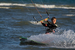 Close up of young man kite boarding in choppy water