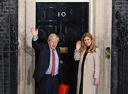 © Licensed to London News Pictures. 13/12/2019. London , UK.  British Prime Minister and leader of the Conservative Party Boris Johnson waves to the members of the media with his partner Carrie Symonds at 10 Downing Street.  Boris Johnson's Conservative Party  wins a majority of seats in Parliament. That outcome would allow Johnson to complete his plan to take the U.K. out of the European Union on the 31st of January 2020. Photo credit: Ioannis Alexopoulos /LNP