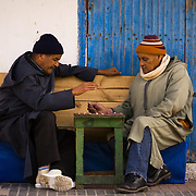 Two old men playing draughts in a Essaouira street