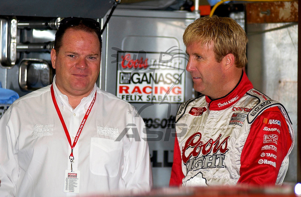 Car owner, Chip Ganassi, talks with his driver, Sterling Marlin, during a practice session for the Sirius 400 NASCAR Winston Cup race at the Michigan International Speedway in Brooklyn, Michigan.