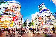 Shibuya crossing at night. Blurred Japanese people cross the road at twilight with many advertising hordings illuminated alll around. Tokyo, Japan.