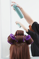 Stylist sprays head of hair with rollers