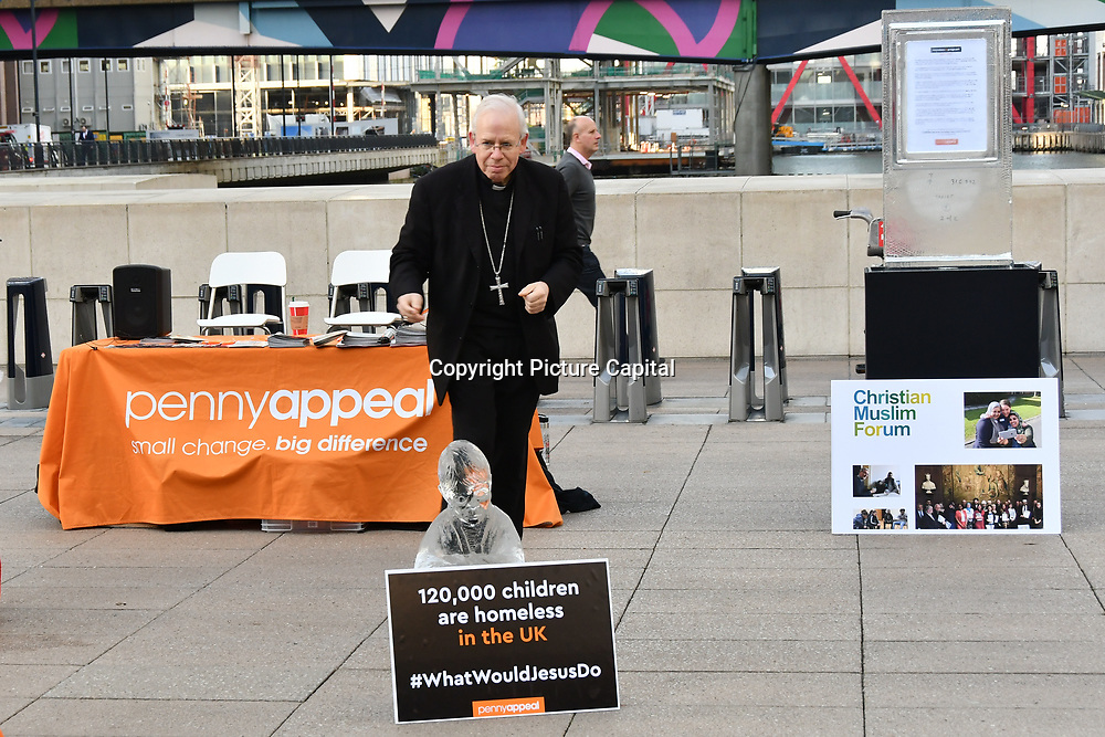"""Speaker Rt Revd Paul Hendricks at Penny Appeal Team Orange unveiling 5 life-size ice statues """"What Would Jesus Do?"""", symbolising homeless families to promote their winter campaign. The frozen family will depict the plight of the 140* families who become homeless everyday, and the 900* children who become homeless every month on 17th December at Canary Wharf, London, UK."""