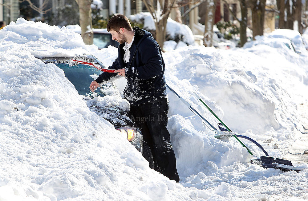 (Boston, MA - 2/10/13) Terre[cq] Delaney of Hyde Park clears a car covered in snow, Sunday, February 10, 2013. Staff photo by Angela Rowlings.
