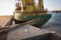 """TRAPANI, ITALY - 7 JUNE 2016: Cargo ship Just Noran, seized by the Guardia di Finanza (Financial Police) in June 2014 as it was carrying 28 tons of hashish from Morocco to Libya, is docked here in the harbor in Trapani, Italy, on June 7th 2016.<br /> <br /> Between January 2014 e December 2015 more than 120 tons of hashish, carried on fishing boats or cargo ships from Morocco to Libya, were seized in the Strait of Sicily by Italy's Guardia di Finanza (Financial Police) thanks to an international police investigation named """"Operazione Libeccio"""", carried out by the GICO (Gruppo Investigativo Criminalità Organizzata, Organised Crime Investigation Group), a unit of the tax police of Palermo under the supervision of the DDA (Direzione Distrettuale Antimafia) of Palermo.<br /> <br /> """"What is happening in Libya is same historical occurrence that happened years ago in Afghanistan. Such as the Talibans who financed their terroristic activities with heroin trafficking for the purchase of weapons, the Caliphate is proposing the same terroristic strategy by purchasing and commercialising hashish in order to purchase weapons used in their war"""" Sergio Barbera, Deputy General Prosecutor of Palermo, said."""